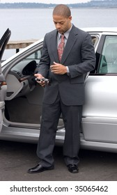 Left handed ethnic business man using a PDA next to his luxury car parked at the lake. He is wearing a suit and tie.