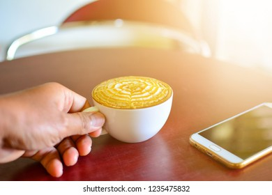 Left handed with latte art coffee and smartphone on table in coffee shop.