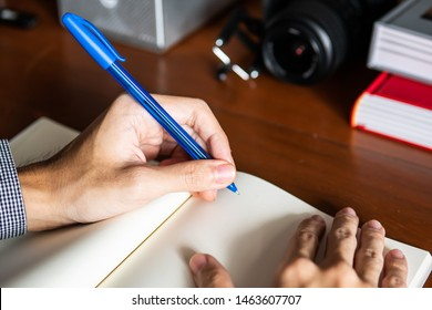 Left handed man writing on notebook