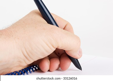 Left handed writer writing on a spiral notebook designed for right handers.