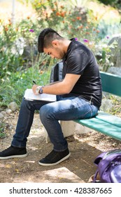 Left handed young man sitting on an outdoor bench, filling out papers