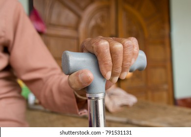 Left hands of old woman asia with a cane walking stick