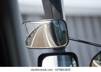 A left modern mirror on a public bus showing clean highway in Nagoya, Japan