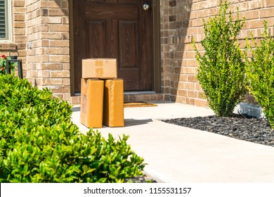 Left Package delivery on doorstep , cardboard boxes left on patio doorstep of nice brick home