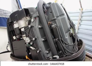 Left side of boat transom four stroke 4 cylinder fuel injection outboard motor close up - electric starter, ignition coils, fuse box, CDI module
