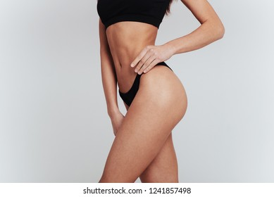 Left side of the body. Girl in underwear with slim figure.