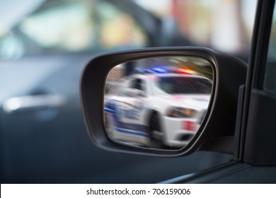 Left side car mirror showing police car in motion