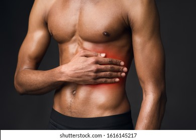 Left Side Pain. Handsome black bodybuilder with red dot suffering from gastritis, sore zone, shirtless torso