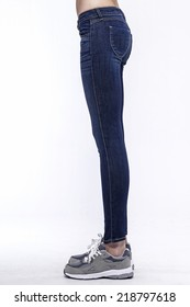Left side view of a standing woman(female) model wearing denim(trousers) isolated on a white background