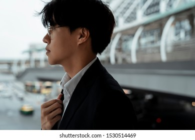 Left side of young businessman walking on a skywalk, the city is a background.