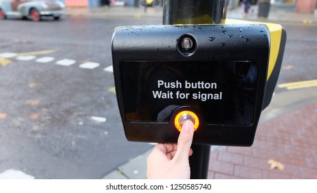 A left thumb pressing a new pedestrian crosswalk signal button on the street side, waiting to cross the road to go to the opposite side.