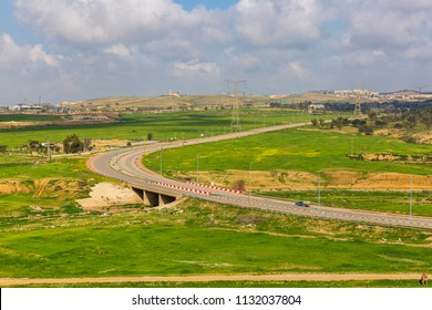 Left turn of road over a green fields with camels