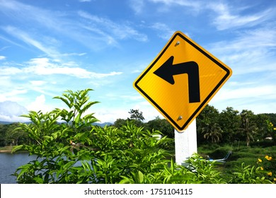 """Left turn sign.Road sign indicating left turn.Yellow traffic sign """"Turn left"""" on the sky background."""