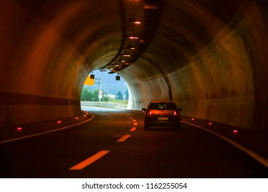 Left two lines curved highway tunnel with one car driving on the right line to the exit on the end.