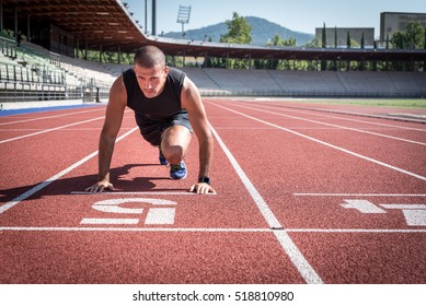 Left view of an athlete starting a run on a running track