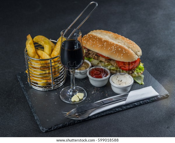 left view on a crusty white bread with sesame seeds, flavored with smoky ribsteak bbq, barbeque sauce, lettuce, tomato, three sauces, chips in a metal basket, liqueur, tasty set