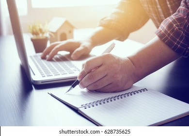 Left-hand manager putting his ideas and writing business plan at workplace,man holding pens and papers, making notes in documents, on the table in office,vintage color,morning light ,selective focus.