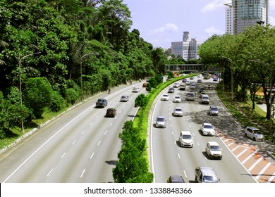 Left-hand traffic. Сars and motorcycles drive along a wide highway on a sunny day in a megapolis (big city) among tropical trees. Singapore view from above