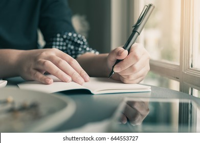 Left-handed woman hand holding pen while writing on small notebook beside window. Freelance journalist working at home concept with vintage filter effect