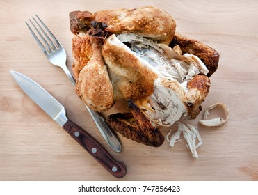 Leftover Chicken Turkey on the bone placed on a wooden board with knife and fork. Poultry carcass with stripped meat