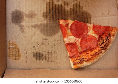 Leftover pepperoni pizza slice in delivery box. Last food piece of popular italian style pizza in greasy used cardbox