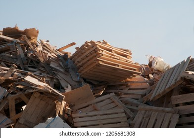 Leftover scraps of wood in a landfill with a blue sky in the background