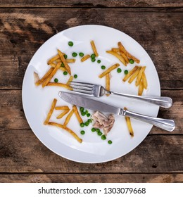 Leftovers of chips peas and chicken on a with plate with knife and fork over a rustic wooden background