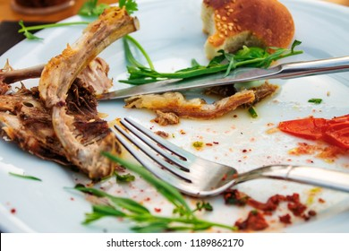 Leftovers and cutlery in plate on table