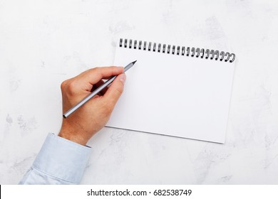 Lefty writes in empty notebook on white table top view. Left handed concept.