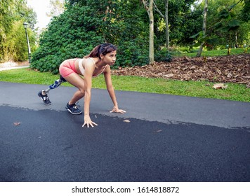 Leg amputated Asian girl working out in nature park to gain body strength