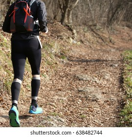 Leg of athlete runner during racing on the mountain trail in winter