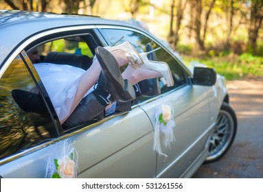 Leg of the bride and groom's leg sticking out of car window
