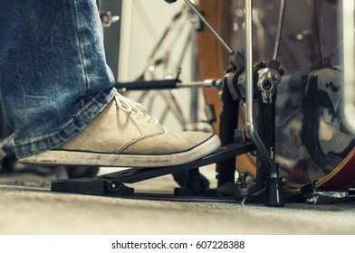 The leg of a drummer in a rock band on a double pedal Playing the bass drum.