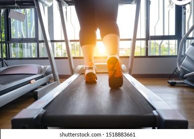 leg of fat woman being run or jog on belt of treadmill machine