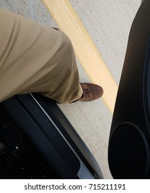 leg and foot stepping out of car