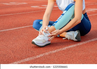 Leg Injury. Woman runner suffering from pain in leg after workout is touching ankle outdoors at stadium