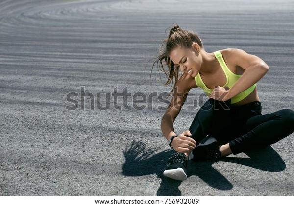 Leg Verletzung. Frauen leiden nach dem Training an Schmerzen in der Leg. Schönes Mädchen in Sportbekleidung Sitzen und berühren schmerzhaften Knöchel verletzt während Training im Freien. Sportverletzung. Hohe Auflösung