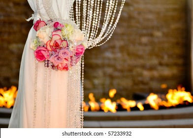 A leg of a Jewish wedding cannopy decorated with beautiful flowers with fire in the background