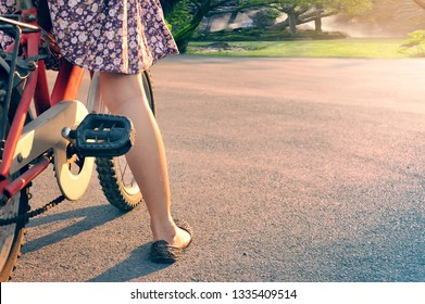 Leg of kid girl prepare to riding bicycle along a road to light destination.Healthy Lifestyle and Well Growth Concept.