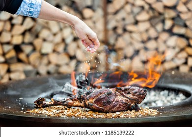 Leg of lamb grilled the Woman salting the meat. selective focus