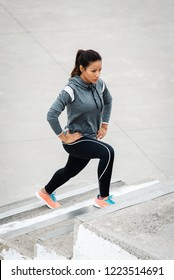 Leg lunges exercise on stairs. Fitness woman working out in the city.
