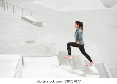 Leg lunges exercise on stairs. Fitness woman working out on urban park.