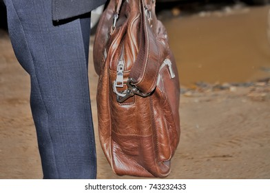 leg man carries a brown leather briefcase bag with money important documents