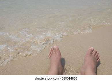 Leg of man sunbathing and relax on tropical beach. in evening time