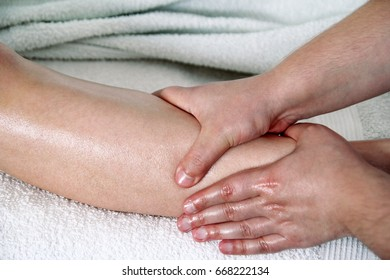 Leg massage. Male masseur therapist hands doing applying pressure kneading on female calf leg massage. Professional masseuse massaging foot of girl. Woman having sports foot massage in spa salon.