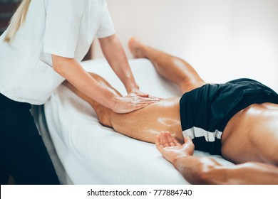 Leg massage. Physical therapyst massaging leg of young male athelete