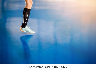 Leg of player and indoor soccer sports hall. Football futsal player, ball, futsal floor. Sports background. Youth futsal league. Indoor football players with classic soccer ball.