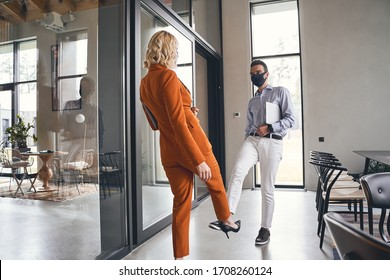Leg shake. Young male in a protective mask greeting his female colleague in the office