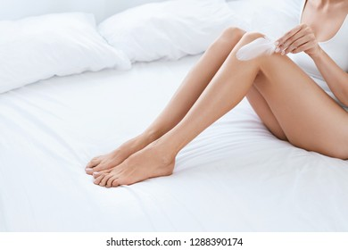 Leg Skin. Woman Touching Legs With Soft Skin With White Feather