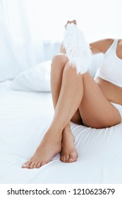 Leg Skin. Woman Touching Long Legs With Smooth Skin With Feather